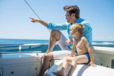 Father and son spending time together on a yacht. Father is showing him something.